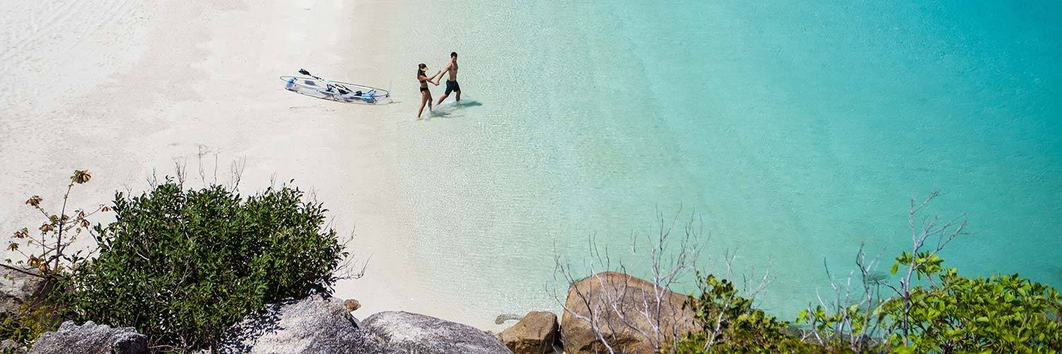 Couple walking in the water on Lizard Island