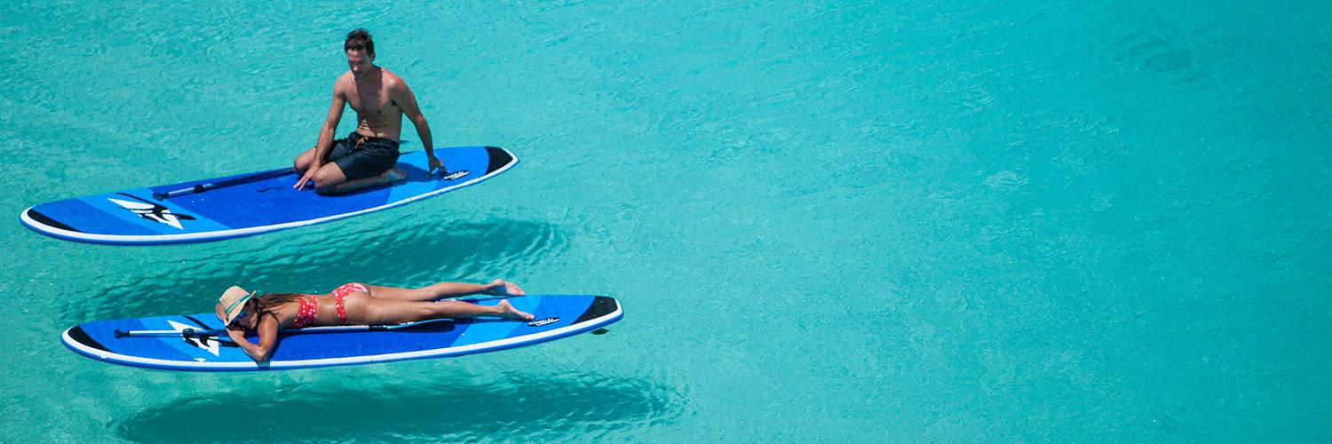 Guest relaxing on paddle boards on Anchor Bay, Lizard Island