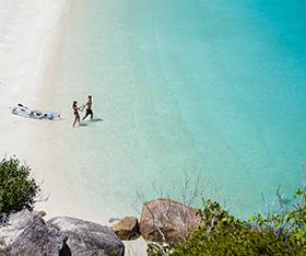 Couple walking on the beach on Lizard Island
